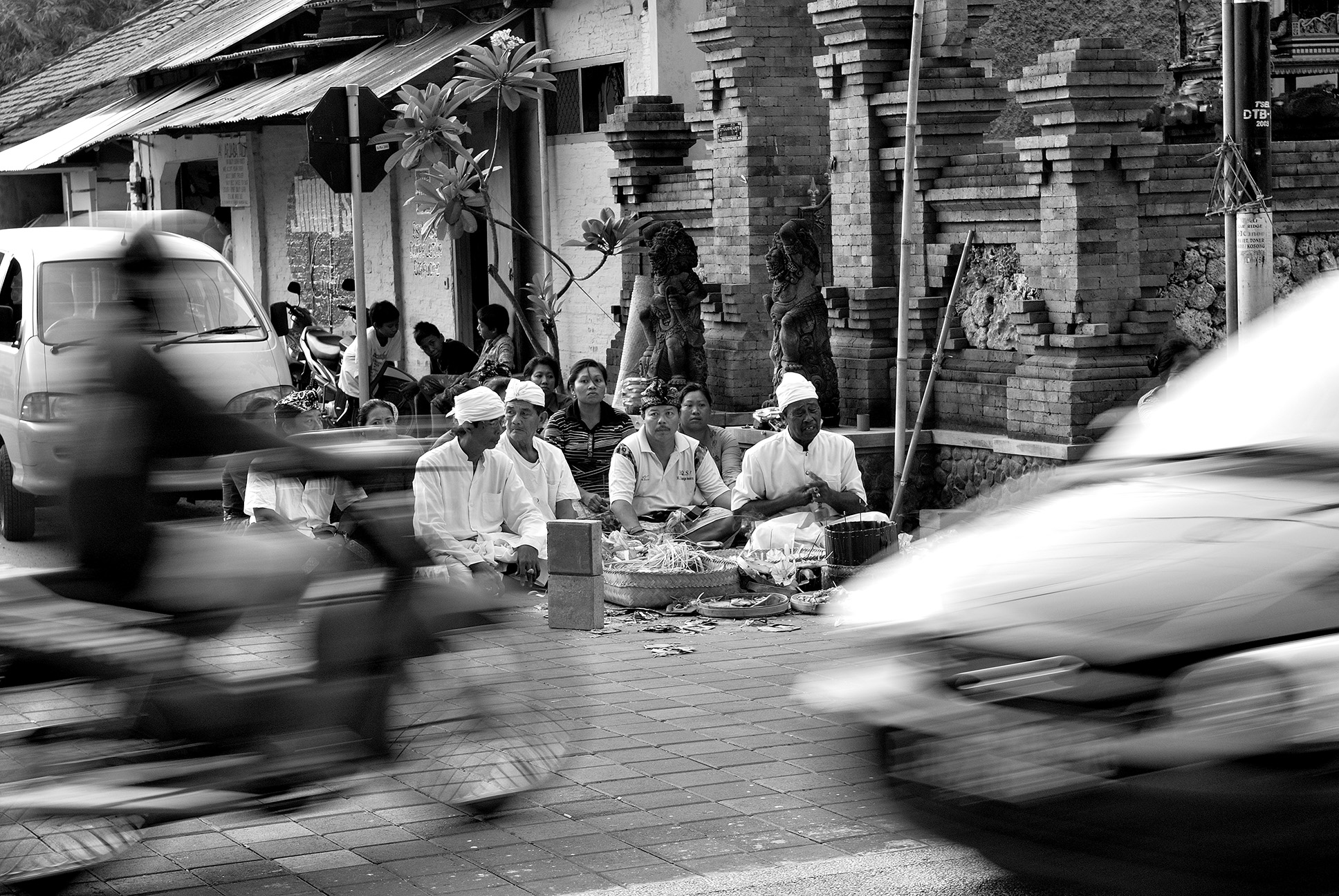 religious ceremony in Bali, at crossroads, as traffic streams by